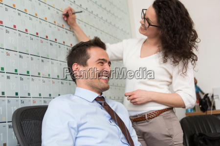 woman writing on wall calendar man