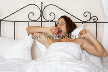 young man yawning in bed