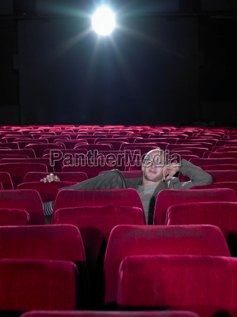 mature man relaxing in empty cinema