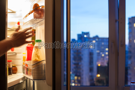hand reaches to refrigerator and view