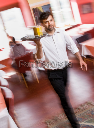 male waiter with drinks in hand