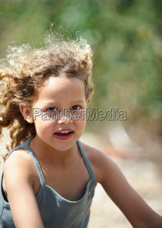 young girl riding bicycle wind in