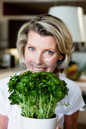 senior woman holding plant