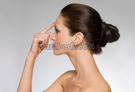 model with finger to forehead