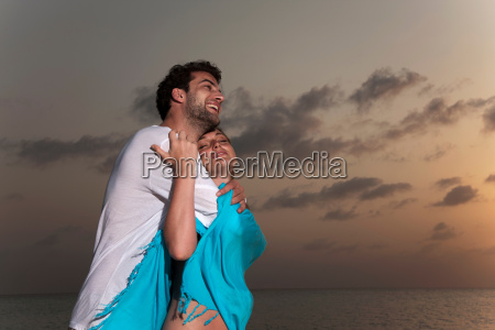couple hugging on beach at sunset