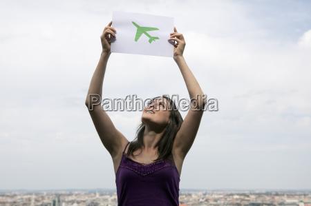 woman lifting paper green plane