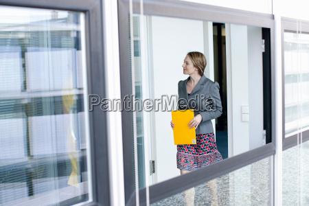 businesswoman, carrying, folder, in, office - 18315448