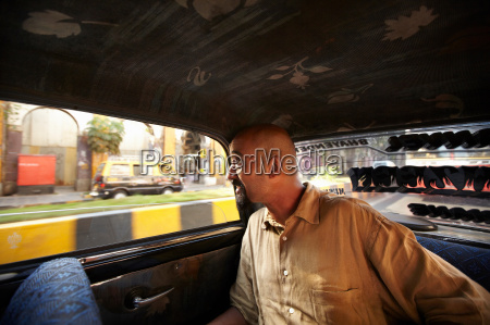 smiling man riding in taxi cab