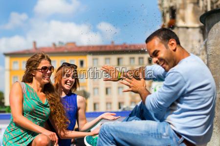 women splashing man with water