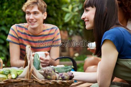 friends sitting in garden with basket