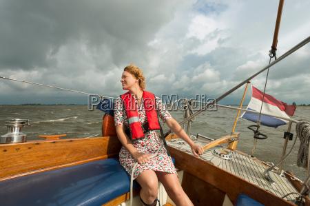 woman steering boat on rocky water