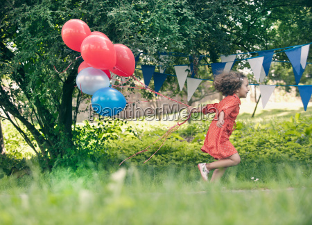 girl holding bunch of balloons outdoors