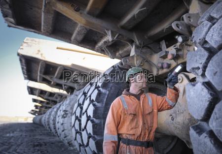 coal miner inspects dumper truck tyre