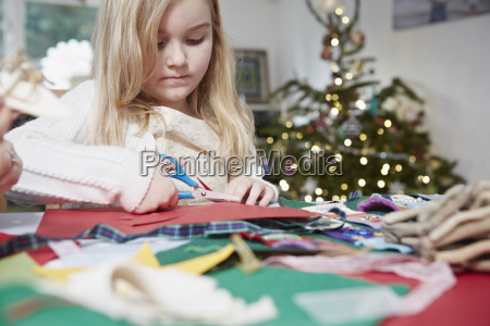 young girl cutting out paper with