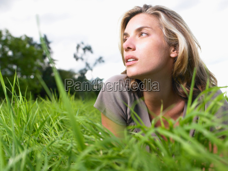 woman laying in a green field