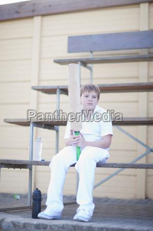 boy holding cricket bat sitting on