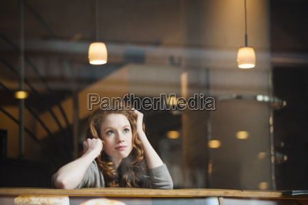 thoughtful young woman sitting alone in