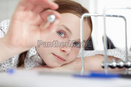 girl playing with newtons cradle on