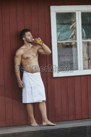 young man drinking a beer outside