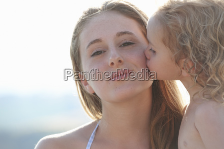 portrait of young girl kissing older