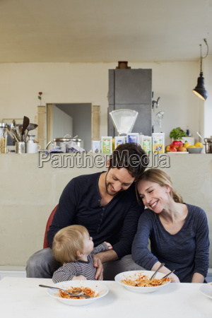 family with baby girl eating spaghetti