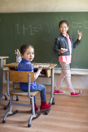 girl by blackboard and sister at
