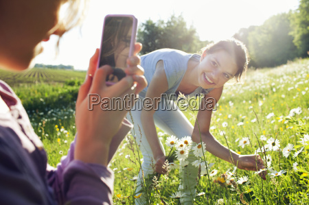 girl taking photograph of girl picking