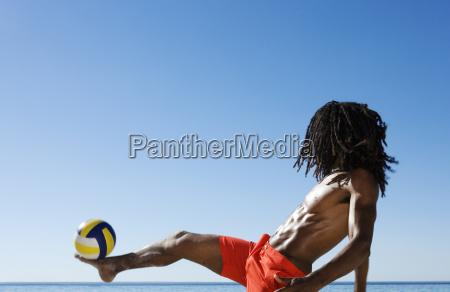 young man balancing football on foot