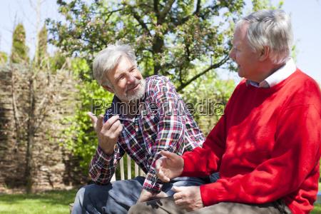 two senior male friends talking
