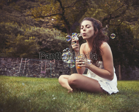 young woman sitting in field blowing
