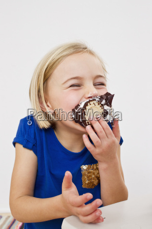 studio portrait of young girl eating