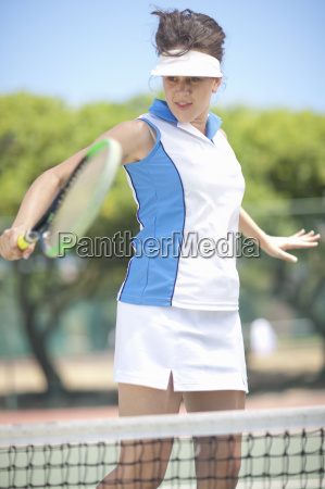 tennis player hitting backhand volley