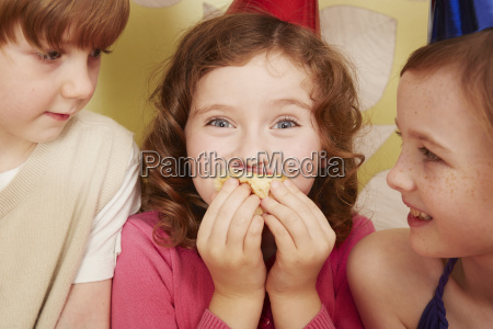 girl eating party food friends watching