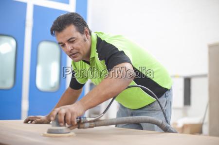man sanding down plank of wood