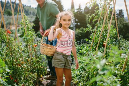 girl holding basket in vegetable garden