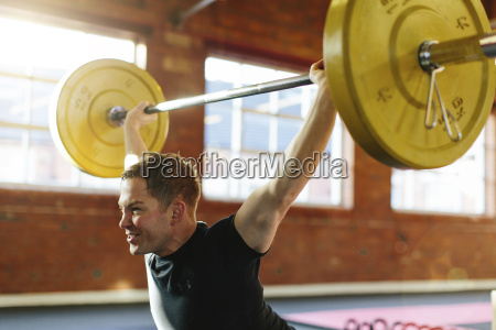 man lifting weights in gymnasium