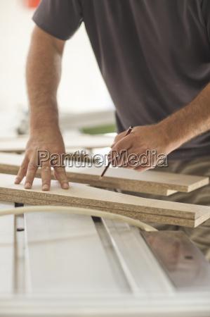 upholsterer measuring planks of wood chip