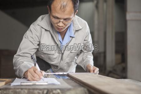 carpenter measuring wood plank with vernier