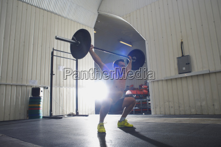 crossfitter lifting barbell in gym