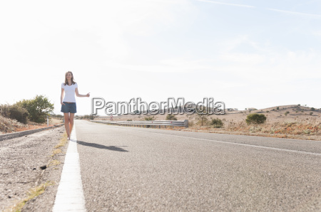mid adult woman hitch hiking on
