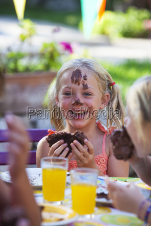 girl eating chocolate cake face covered
