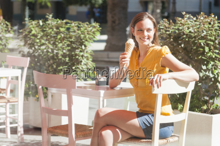 mid adult woman sitting in sidewalk