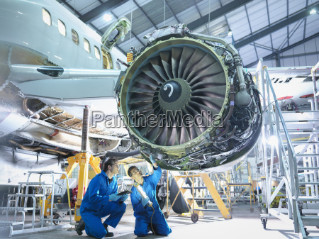 aircraft engineers inspecting jet engine in