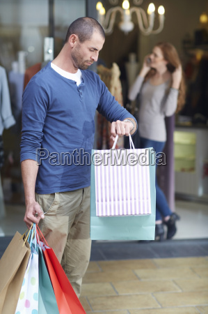 young woman shopping man outside holding