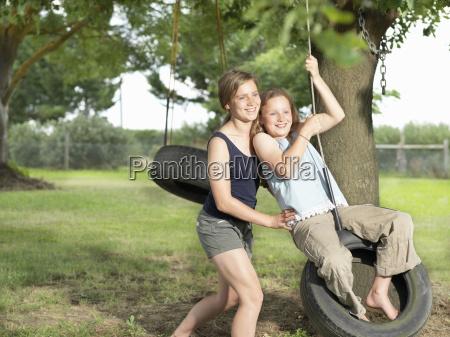 teenage girl pushing her sister on
