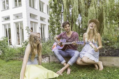 three friends in garden man playing