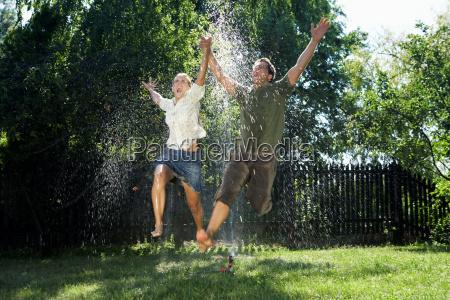 man and women jumping over sprinkler