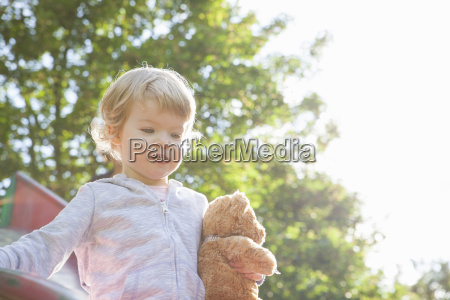 female toddler holding teddy bear playing