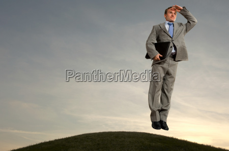 businessman hovering above hill