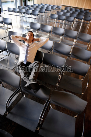 businessman relaxing in empty conference